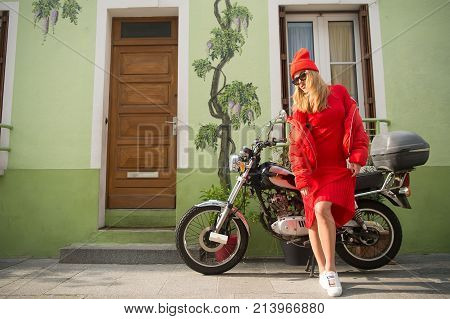 Woman biker at bike transport. Look and retro style. Beauty and vintage fashion. parisian fashion model near house and motorcycle. girl in fashionable red dress hat and glasses france.