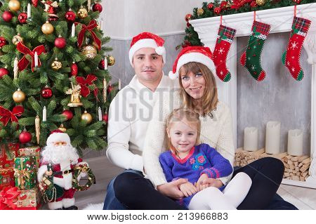Christmas or New year celebration. Happy young family sitting near Christmas tree with xmas gifts. A fireplace with christmas stocking on background