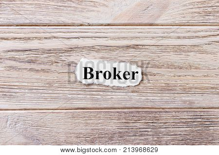Broker of the word on paper. concept. Words of Broker on a wooden background.