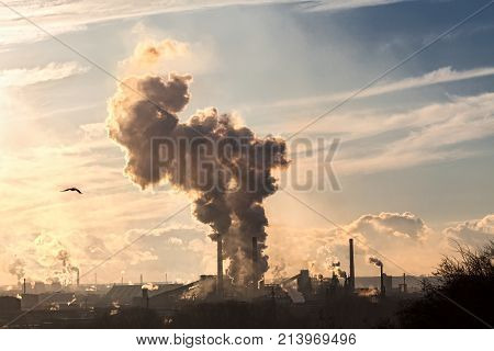 a huge factory. many pipes smoke black smoke in the blue sky. violation of environmental cleanliness. horizontal frame. ecological catastrophy. Apocalypse