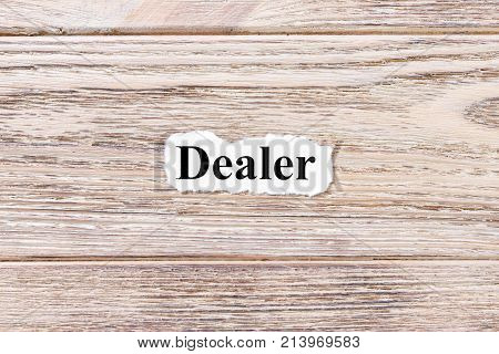 DEALER of the word on paper. concept. Words of DEALER on a wooden background.