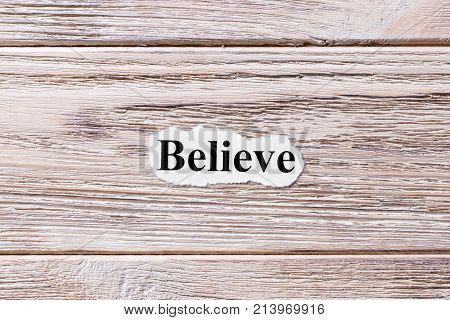 believe of the word on paper. concept. Words of believe on a wooden background.