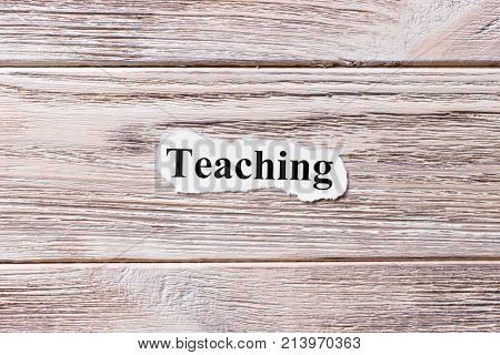 Teaching of the word on paper. concept. Words of Teaching on a wooden background.