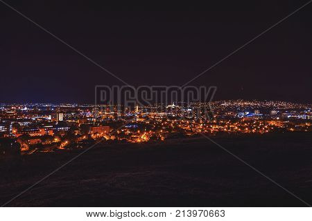 City night in Nitra from the view point on top of Hill (mountain). Slovakia. Slovak city Nitra with purole night sky. City center at night with buildings and churches. City at night (faded)