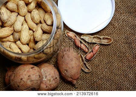 Pelled Peanuts And Peanuts In Glass Jar  With Wild Yam On Old Brown Hemp Sack Background