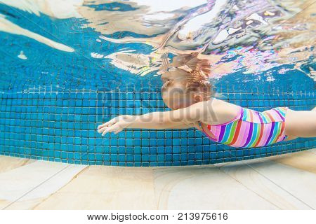 Funny portrait of child learn swimming diving in blue pool with fun - jumping deep down underwater with splashes. Healthy family lifestyle kids water sports activity swimming lesson with parents.