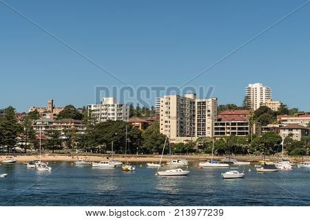 Sydney Australia - March 26 2017: Plenty of mostly white yachts on blue water of North Harbour in front of Manly boardwalk at Cabbage Tree Bay and beach. Clear blue sky and condominiums on shore.