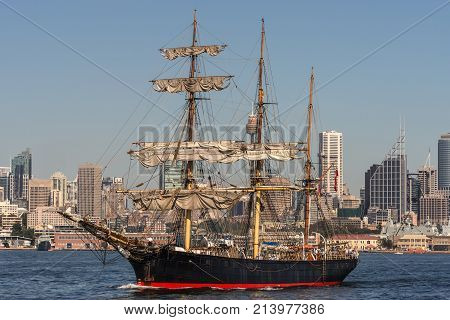 Sydney Australia - March 26 2017: Sailing tall black and red ship with downtown skyline in back ground on blue water and under clear skies.