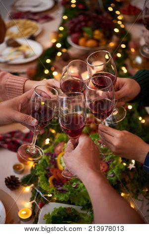 Group of people celebraiting New Year. They are drinking red wine