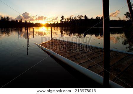 sunset over a decrepit dog amongst a lake in northern minnesota