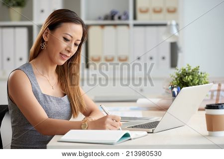 Asian business lady filling her planner for the week