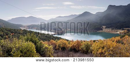 Mountain landscape. Scenic view of a mountain lake Feneos, mountains and autumn trees on a sunny day (mountain Corinthia, Greece)