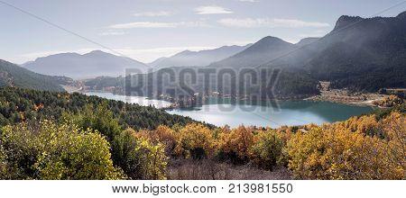 Mountain landscape. Scenic view of a mountain lake Feneos, mountains and autumn trees on a sunny day (mountain Corinthia, Greece)
