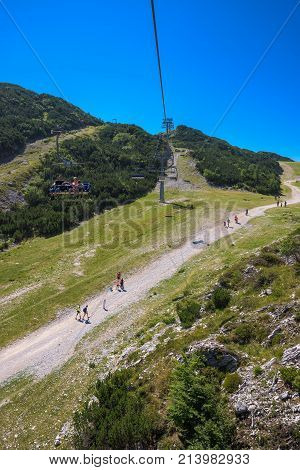 VOGEL MOUNTAIN SLOVENIA - AUGUST 30 2017: Aerial view of unidentifiable group of mountain hikers walking along footpath in popular travel destination for outdoor sports.