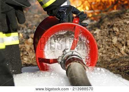 holds a fire hose to extinguish a fire.Extinguish the fire. Fire hose