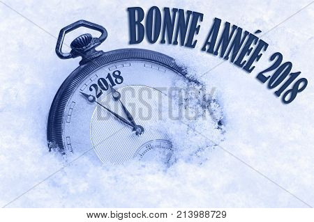 Happy New Year 2018 greeting in French language bonne annee text, pocket watch in snow, 2018 greeting, 2018 new year