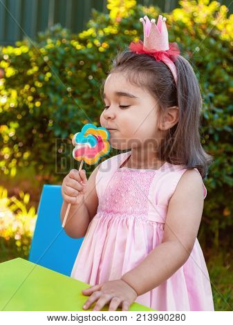 Happy baby toddler girl smelling and savoring a large colorful lollipop smell, scent or aroma dressed in pink dress as princess or queen with crown