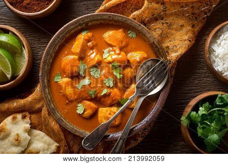 A bowl of delicious indian butter chicken curry with naan bread basmati rice and cilantro garnish.