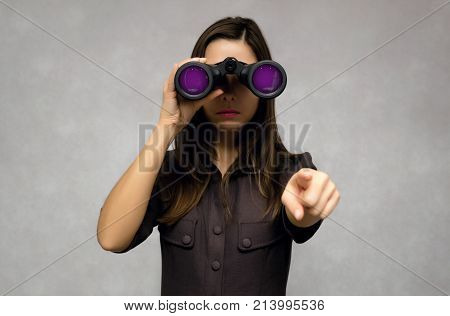 Young caucasian woman looking through binoculars with glamour purple lens and showing ahead by her index finger. Find and search. Find something interesting.