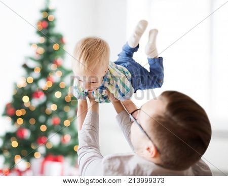 family, fatherhood, holidays and people concept - happy father and little son playing and having fun at home over christmas tree background