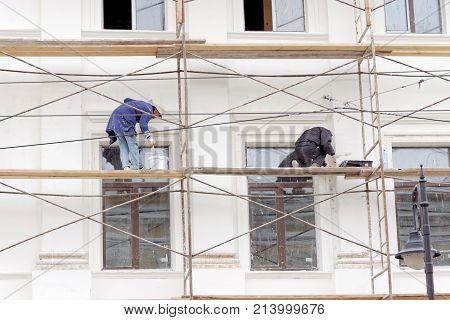 Nizhny Novgorod Russia. - October 03.2017. Repair of Nizhny Novgorod regional dermatovenerologic dispensary in Rozhdestvenskaya street 42. Workers on scaffolding paint the wall.