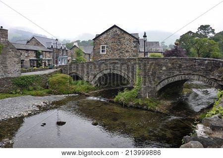 Stone bridge and the River Glaslyn Afon Glaslyn at the centre of Beddgelert village in Snowdonia Gwynedd Wales UK.