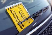 Penalty charge notice parking fine attached to car windscreen poster