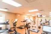 Blurred image of fitness center with cardio machines weight strength training equipment medical ball and large mirror. Empty gymnasium facility service room in hotel in Texas USA. Active lifestyle poster