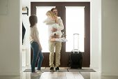 Happy father arrived home returning after business trip with baggage, daddy missed little daughter holding in arms hugging girl while wife standing in hall, family reunion, welcome back dad concept poster