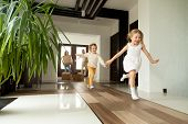Happy young family with cardboard boxes in new home at moving day concept, excited children running into big modern own house hallway, parents with belongings at background, mortgage loan, relocation poster