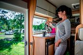 Woman cooking in camper, motorhome interior. Family vacation travel, holiday trip in motorhome RV, Caravan car Vacation. poster