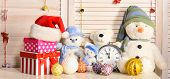 Toys placed on bureau on wooden wall background. Christmas decorations in festive room. Snowmen teddy bears Christmas balls and present boxes near alarm clock. Celebration and New Year decor concept poster