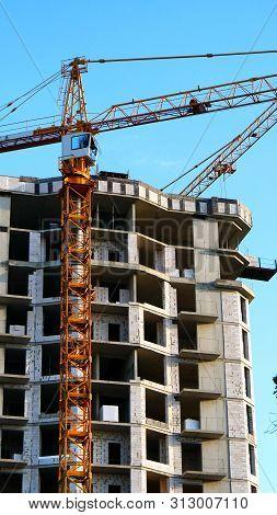 Building Under Construction. Construction Site. Crane Near Building.
