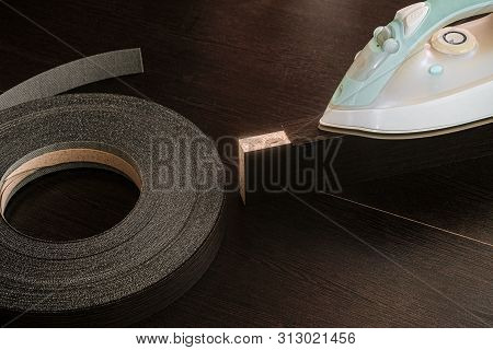 Roll melamine edge for finishing of furniture and hot smoothing-iron used for gluing edges. Edging tape on laminated chipboard sheets wenge color. poster