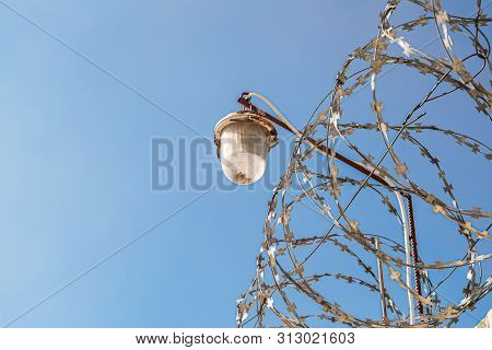 Barbed Wire On A Fence With Outdoor Lamp. Barbwire On Daylight Blue Sky Background.