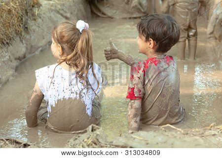 Two Happy Totally Dirty Children Are Sitting And Playing In A Liquid Muddy Potter Clay Improvised Ba