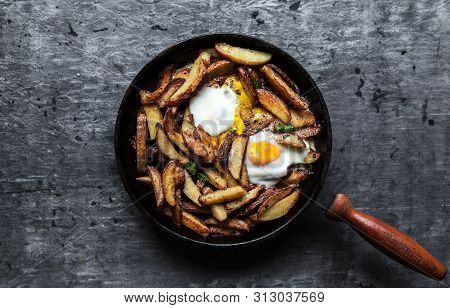 Fried Potatoes With Meat, Ham And Eggs In A Pan Close-up. Horizontal