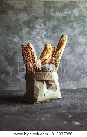 French Pastries, Baguettes On A Gray Background In A Paper Bag. A