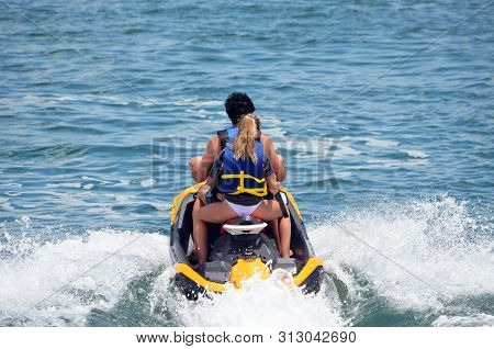 Angled Overhead View Of A Young Boy And A Young Girl Riding Tandem On A Speeding Jetski.