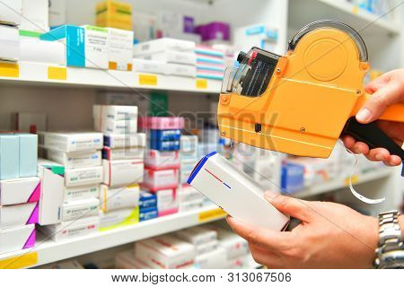 Hand Of The Pharmacist Using Yellow Labeling Gun For Sticking Price Label Of Medicine In Pharmacy Dr
