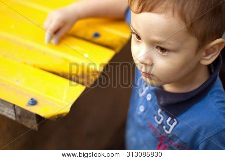Dirty boy with cute eyes. Nasty boy outdoors in blue t-shirt near the yellow background