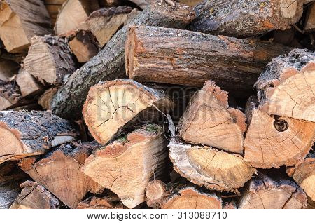 Pile Of Stacked Triangle Firewood Prepared For Fireplace And Boiler. Background With Pile Of Firewoo