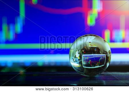 Arrangement Of World Globe Crystal Glass At Office Table On Charts Stock Data On Computer Screen Bac