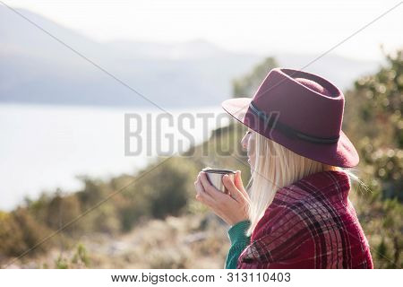 Woman Traveler Drinks Coffee In Autumn Mountains Above Sea. Cozy Fall Picnic On Beach. Girl In Warm