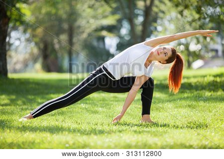 Yoga outdoor. Happy woman doing yoga exercises, stretching in the park. Yoga meditation in nature. Concept of healthy lifestyle and relaxation. Pretty woman practicing yoga on the grass
