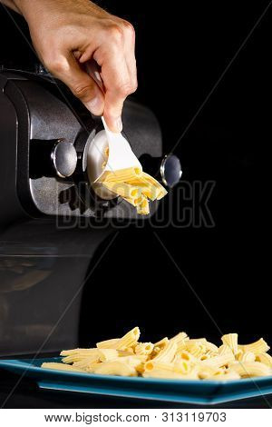 Home Made Pasta By Pasta Maker. An Indifinited Man Cutting The Rigatoni