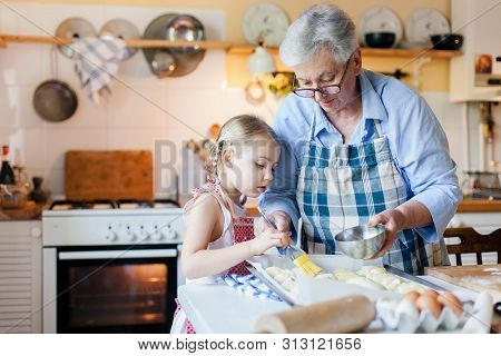 Family Is Cooking In Cozy Home Kitchen. Grandmother And Child Are Using Oven. Retired Woman And Litt