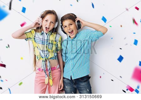 A portrait of two cheerful young kids listening to music in headphones over the white background. Summer casual kids fashion.