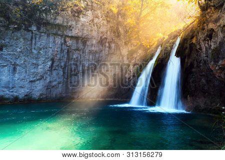 Sunbeams on amazing waterfall in Plitvice lakes. Plitvice National Park, Croatia. Landscape photography