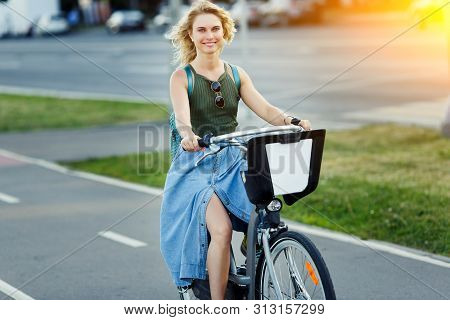 Photo Of Happy Blonde In Long Denim Skirt Riding Bike On Road In City On Summer Day, Sunflare Effect